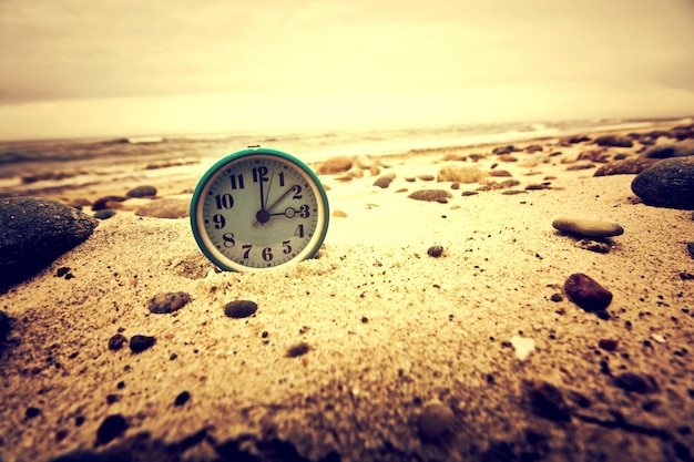 Clock on the beach. time and business concept. Free Photo
