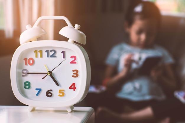 Clock and child playing smartphone. Premium Photo