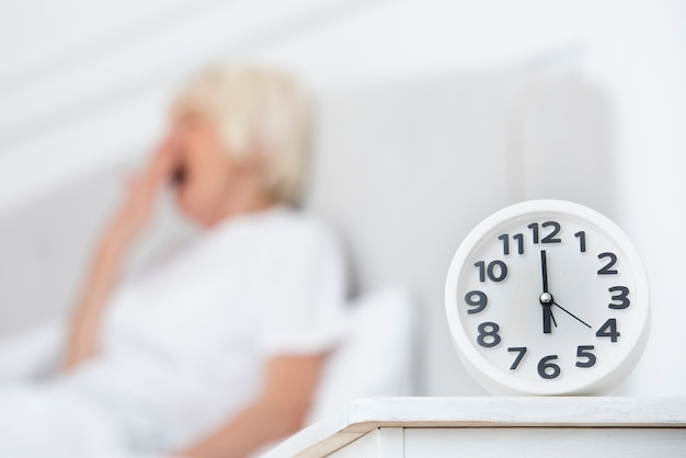 Clock and elder woman on blurred background Free Photo