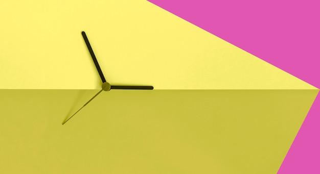 산 분홍색과 노란색 컬러 블록 배경에 시계 손. 여름 시간 개념입니다. 계절의 시간 변화. 시간 개념. 공간을 복사하십시오. 프리미엄 사진