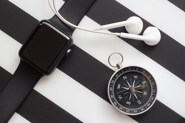 Часы, наушники и компас на черном и белом фоне Premium Фотографии