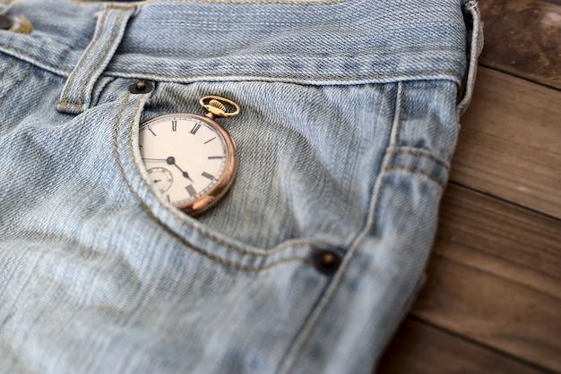 木製の表面-時間管理の概念のジーンズのポケットの時計 無料写真