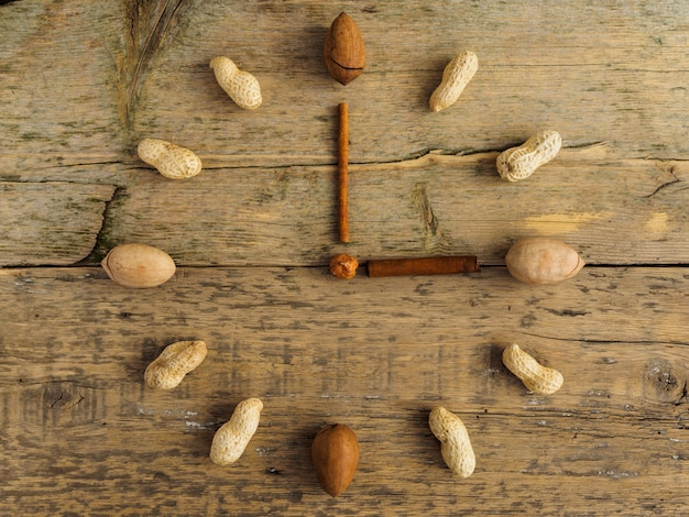 Clock made of different nuts and cinnamon on wooden table Premium Photo