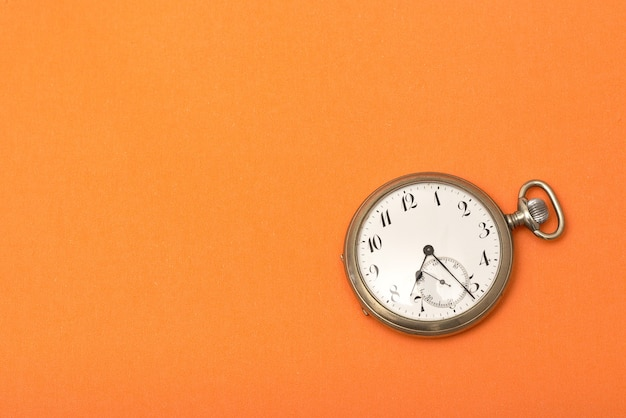 Clock on an orange surface - time management concept Free Photo