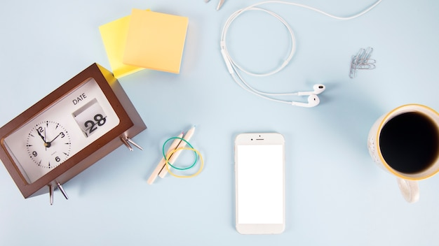 Clock and school supplies near smartphone and drink Free Photo