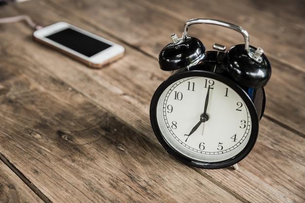 Часы раз в 7 часов утра на деревянный стол с смартфон зарядки в кафе размытие фона. Premium Фотографии