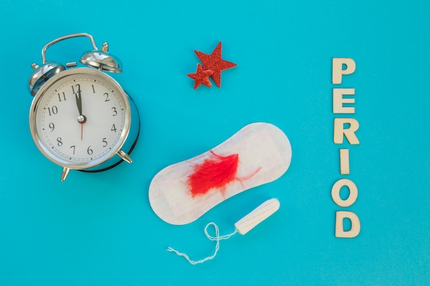 Clock with sanitary towel and tampon Free Photo