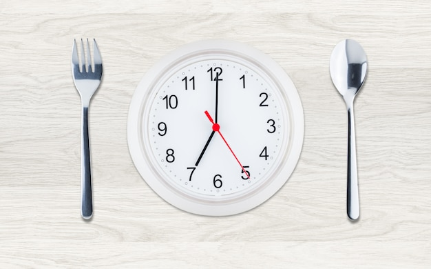 Clock with utensils on clean wood background, flat lay composition Premium Photo