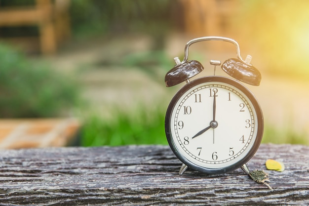 Clock on wood table with green nature background time at 8 o'clock morning Premium Photo
