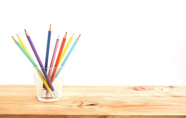 Clorful pencil in glass on wood bar table background Premium Photo