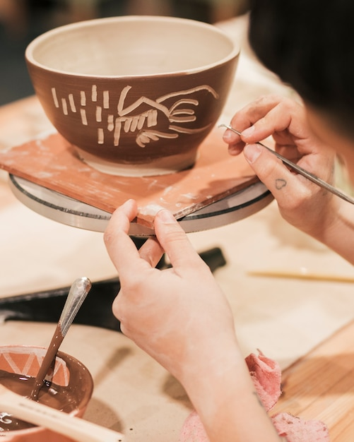 Clos-up of female potter's hand carving on the bowl Free Photo