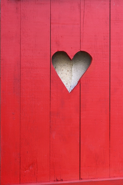 Close on a heart-shaped on a red wooden shutter Premium Photo