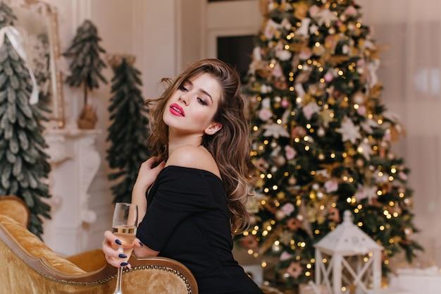새해 장식에 대한 축제 분위기에서 맛있는 와인을 즐기는 밝은 입술로 유럽 외관의 매력적이고 세련된 여성의 실내 초상화를 닫습니다. 무료 사진