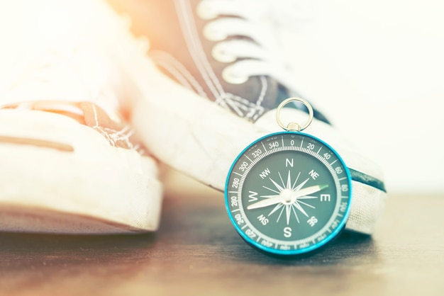 Close-op of compass and sneakers on wood with sunset light. Premium Photo