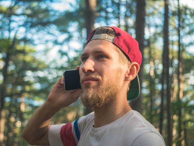 Close portrait of young bearded hipster in cap talking via phone walking in nature frest in europe switzerland Premium Photo