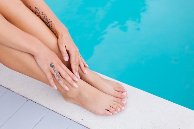 ショットの女性の足と手を閉じます。女性は休暇中に青いプールの端に座る 無料写真