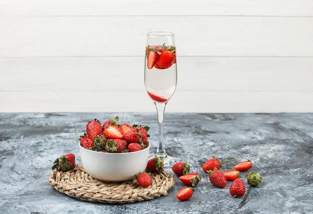 ダークブルーの大理石と白い木の板の表面に飲み物のグラスと丸い籐のプレースマットにイチゴのボウルをクローズアップ。水平 無料写真