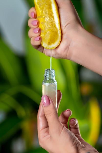 Крупный план: женская рука сжимает сок из лимона в стеклянную бутылку. натуральная косметика Premium Фотографии