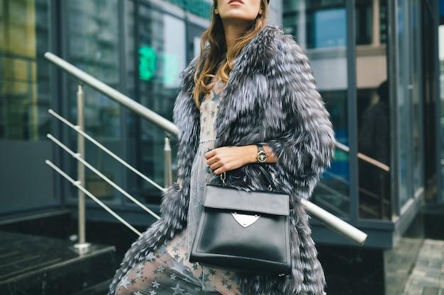 Закройте детали аксессуаров стильной женщины, гуляющей по городу в теплой шубе, держащей черную кожаную сумку, зимний сезон, Бесплатные Фотографии