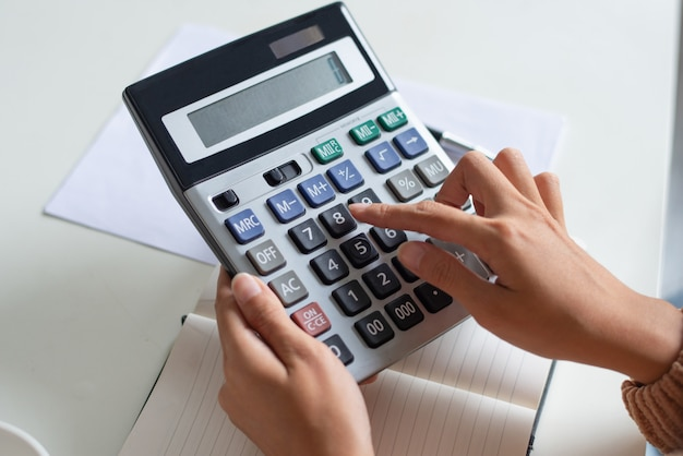 Close-up of accountant using calculator while examining report Free Photo