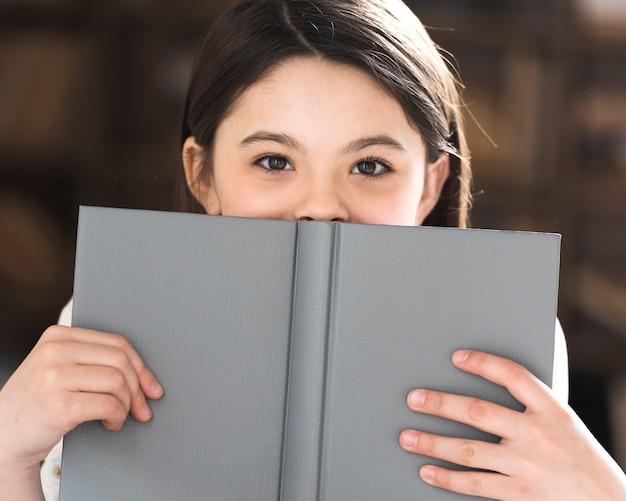 Bambina adorabile del primo piano che tiene un libro Foto Gratuite