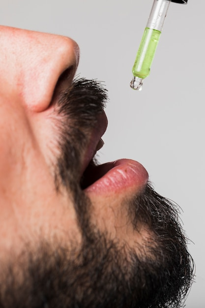 Close-up adult male swallowing drops Free Photo