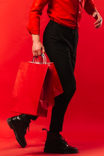Close-up adult man holding shopping bags Free Photo