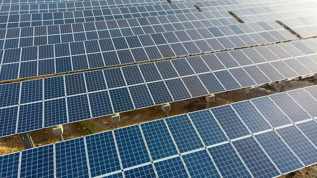 Close up aerial view over solar panels farm (solar cell) with sunlight. Premium Photo