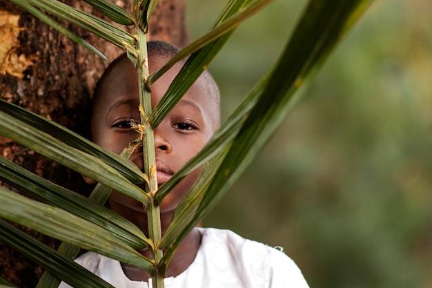葉を保持しているアフリカの子供をクローズアップ Premium写真