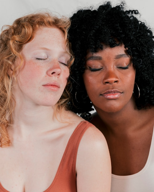 Close-up of an african and blonde young women with eye closed Free Photo