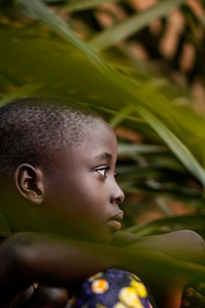 葉でポーズをとってクローズアップアフリカの子供 無料写真