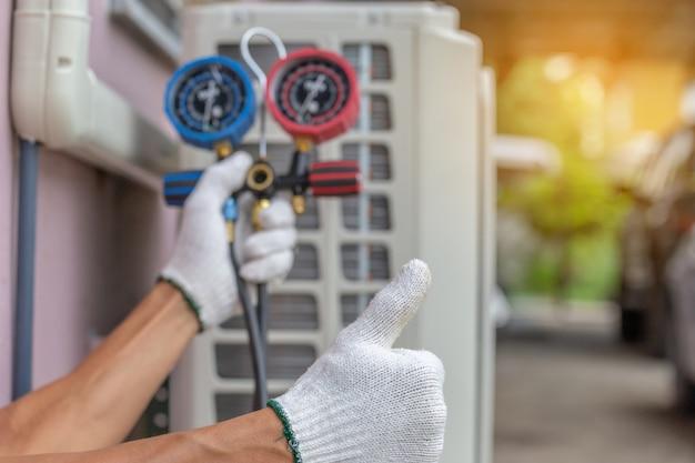 Close up of air conditioning repair, repairman on the floor fixing air conditioning system Premium Photo