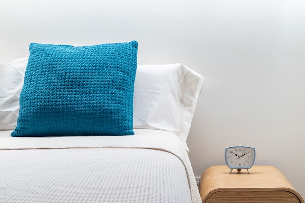 Close-up of alarm clock on a night table next to a sleeping bed Premium Photo