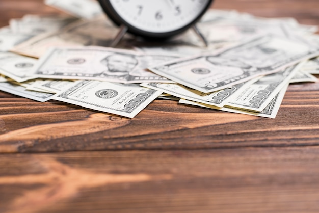 Close-up of alarm clock over the us dollar currency notes on wooden desk Free Photo