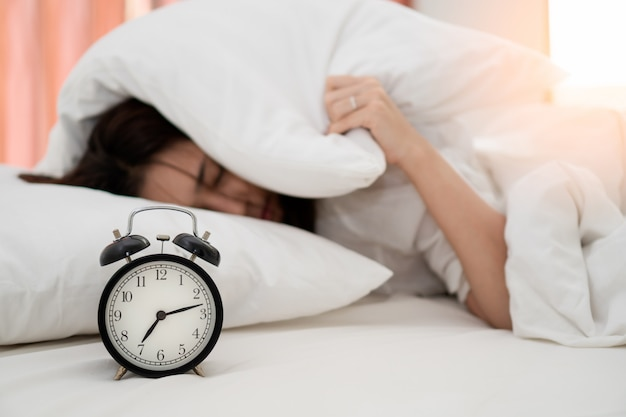 Premium Photo | Close up alarm clock with young asian woman lazy waking up  in early morning for routine daily job.