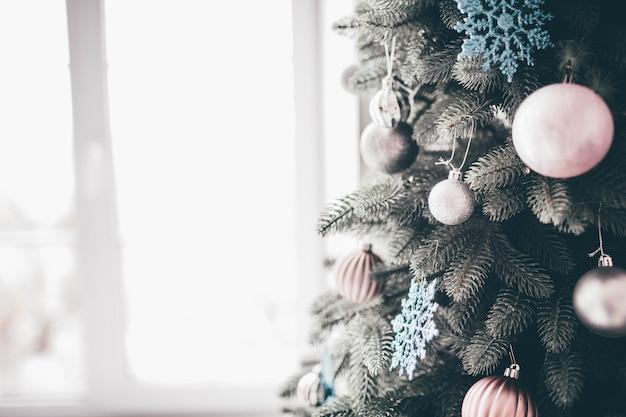 新年の準備ができているクリスマスツリーの装飾された部分のクローズアップとカットビュー。木の周りのピンクと白の装飾。 Premium写真