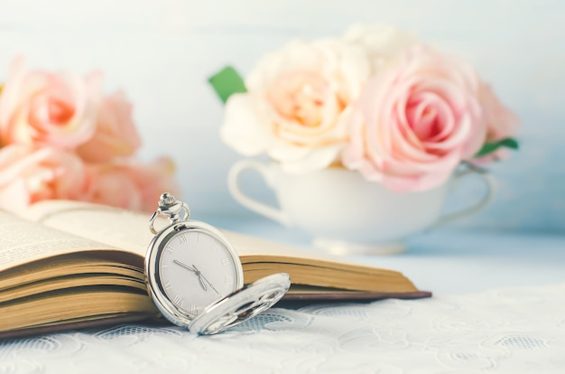 Close up of antique silver pocket watch and opened book with rose flowers on white and blue Premium Photo