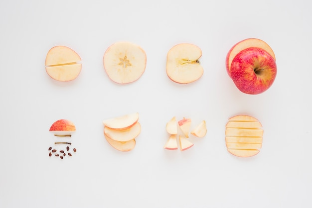 Close-up of an apple cuts into various slices on white background Free Photo