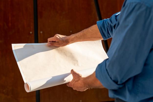 Close-up of architect holding plan Free Photo