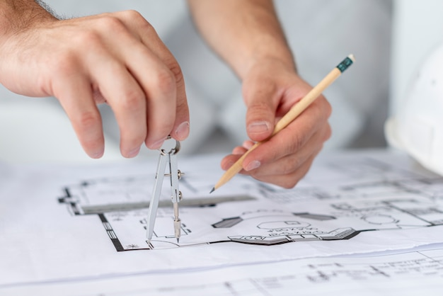 Close-up architect using a compass and a pencil Free Photo