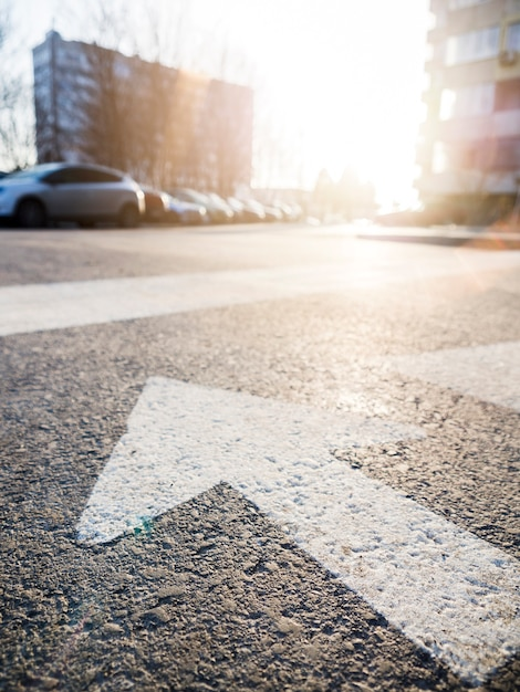 Close-up of arrow on asphalt with view of the street Free Photo