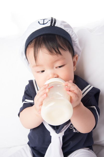 Close up of asian baby infant drinking mother breast feeding from bottle Premium Photo