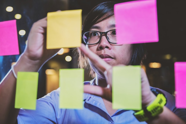 Close up asian businesswoman writing a plan on sticky notes Premium Photo