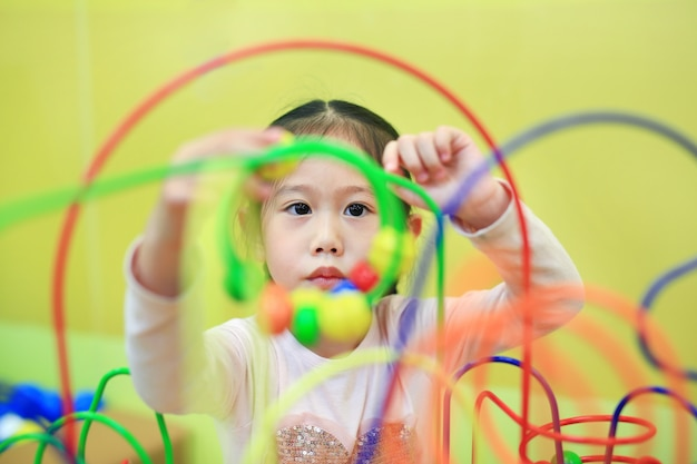 Close-up asian child girl playing educational toy for brain development at kids room. Premium Photo
