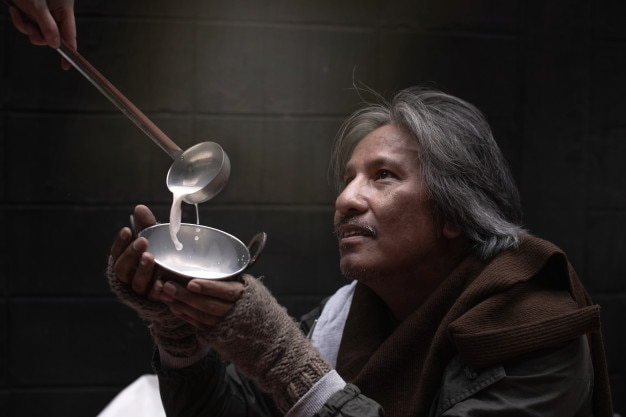 Close up of asian vagrant or homeless hand holding a cup and feel happy with the donated food Premium Photo