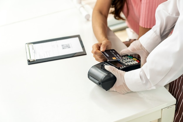 Close up asian woman customer make contactless credit card payment after eating out in new normal social distance restaurant to reduce touching. online contactless and technology concept. Premium Photo