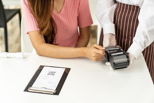 Close up asian woman customer make contactless credit card payment Premium Photo