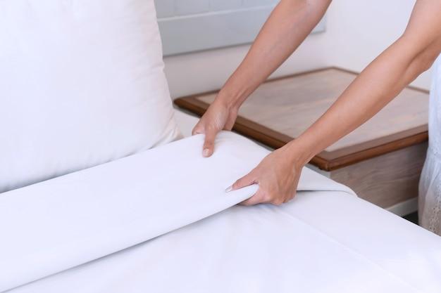 Крупным планом азиатские руки женщины устанавливают белую простыню в гостиничном номере Premium Фотографии