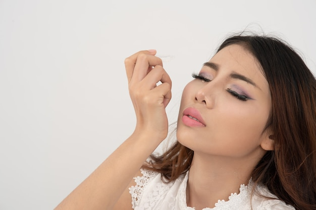 Close up asian woman using eye drop, thai woman dropping eye lubricant to treat dry eye or allergy; young female getting the medicine in the eye on white background. Premium Photo