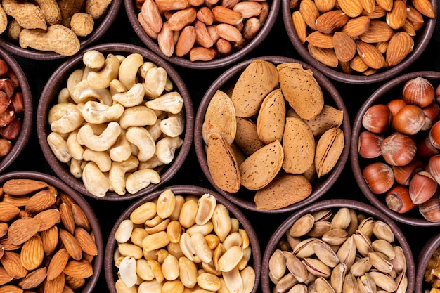Close-up assorted nuts and dried fruits in mini different bowls with pecan, pistachios, almond, peanut, cashew, pine nuts Free Photo